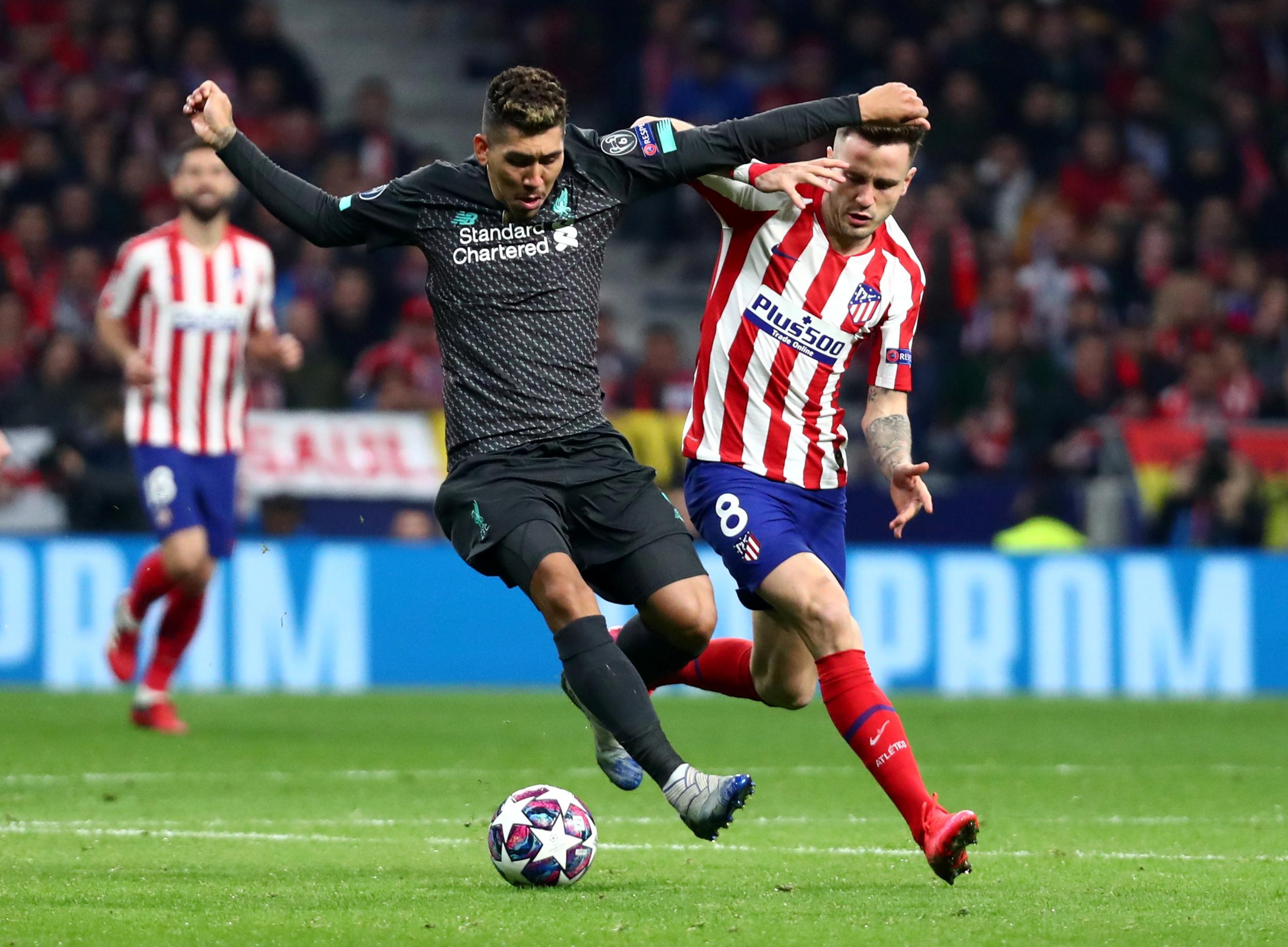 马德里竞技队球员萨乌尔(右)和利物浦队球员菲尔米诺在比赛中拼抢